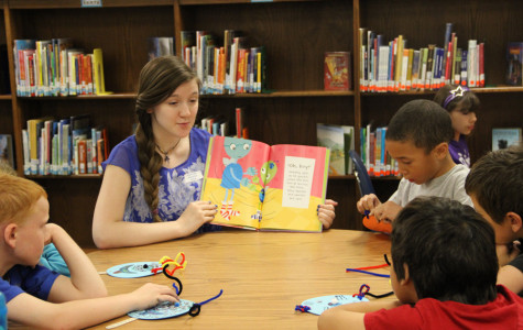 Junior Alisha Keller reading to the younger students.