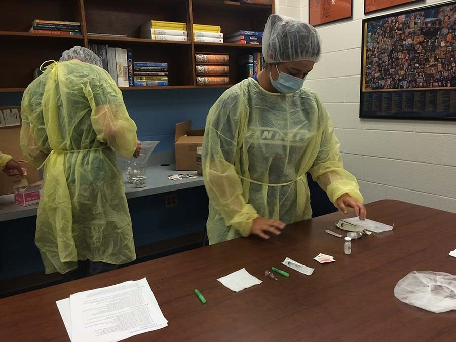 Students work with pharmacy items to prepare for the upcoming certification test.