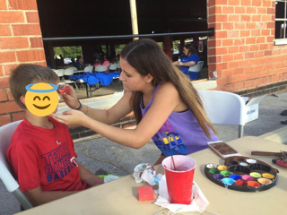 Student Kaitlyn Dockery paints a boy's face at the Hope for Hudson Hutchins benefit