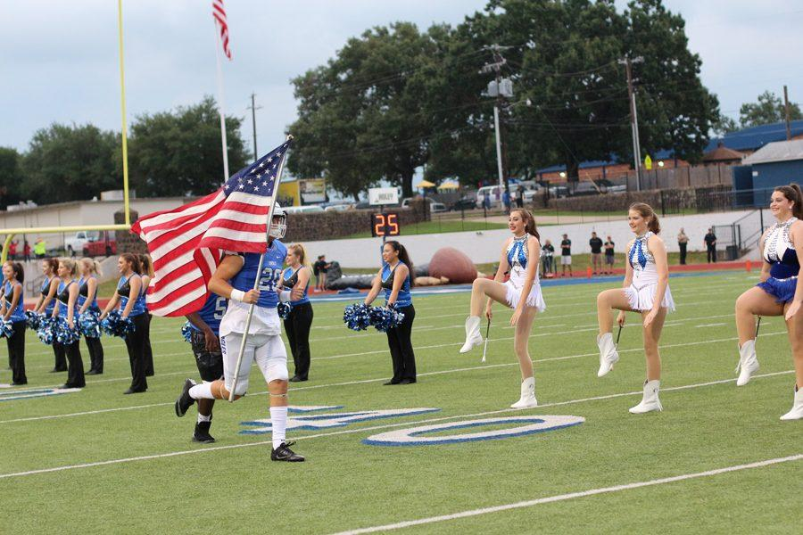 Player carries out the American Flag after coming through the blimp before the game.