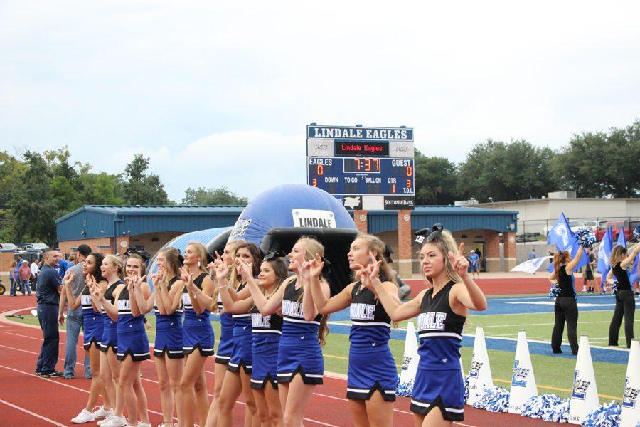 Cheerleaders+lock+hands+on+the+sidelines+before+the+start+of+a+game.