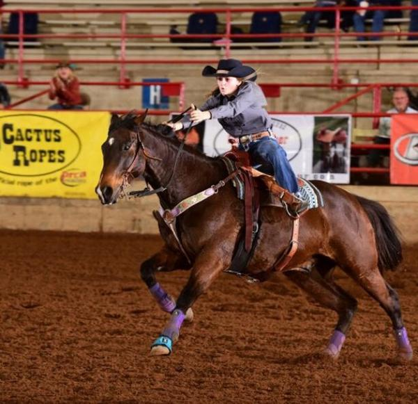 Laramie Wedemeyer rides her horse in a rodeo competition.