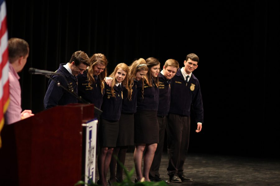 FFA Students gather on stage in a moment of shared emotion.