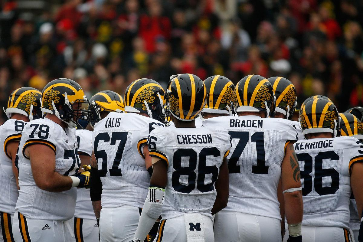 The University of Michigan's 2015 Wolverines in a pre-game huddle. The team is one of few that generate over one hundred thousand fans per game, on average.