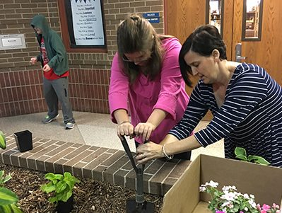 Jan Simmons and Lauren Abrameit dig in the dirt in order to revitalize the empty planter in the main hallway.