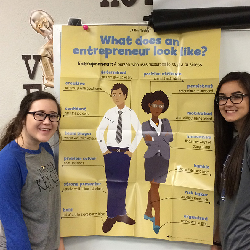 Annie Evans and Makenna Crews prepare to teach class. They taught elementary students concepts about entrepreneurship and business marketing.
