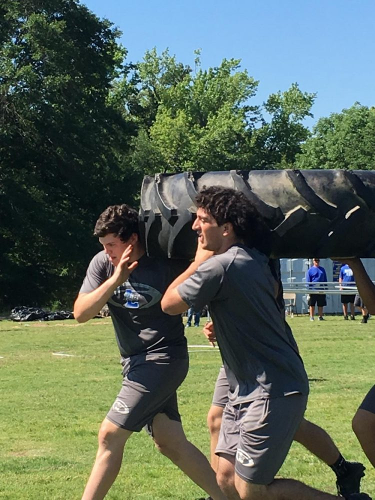 Sophomore James Sandifer and junior Kyle Reed compete in the obstacle course portion of lineman challenge.