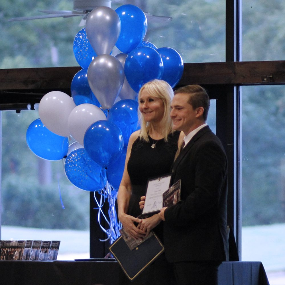 Corban Sorrells and the teacher he selected, Laurie Streich, receive honor at the banquet. Sorrells was sixth in his class this year.