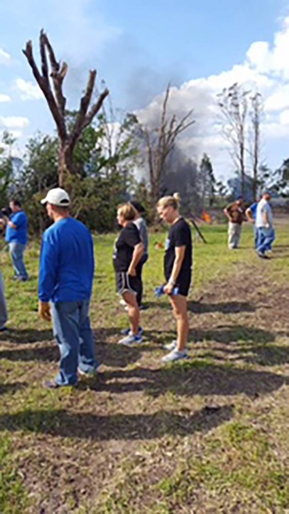 Coaches assist the students in picking up debris. They cleaned up most of the yard in only a few hours.
