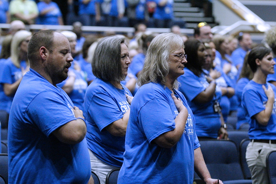 Staff members stand to recite the pledges. The pledges were led by student council member Logan Hale.