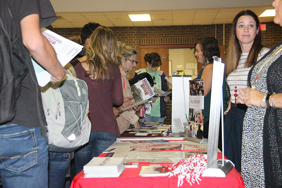Students approach the tables of various colleges to receive information. Representatives from several schools came to inform the students on the individual benefits of each college.
