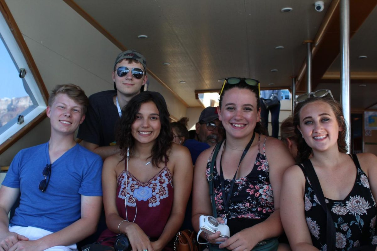 Coleman Allen, Morgan Droblyn, Addison Baquet, and Julia Austin smile as they enjoy a Greek cruise. The cruise toward the local islands and Mediterranean setting.