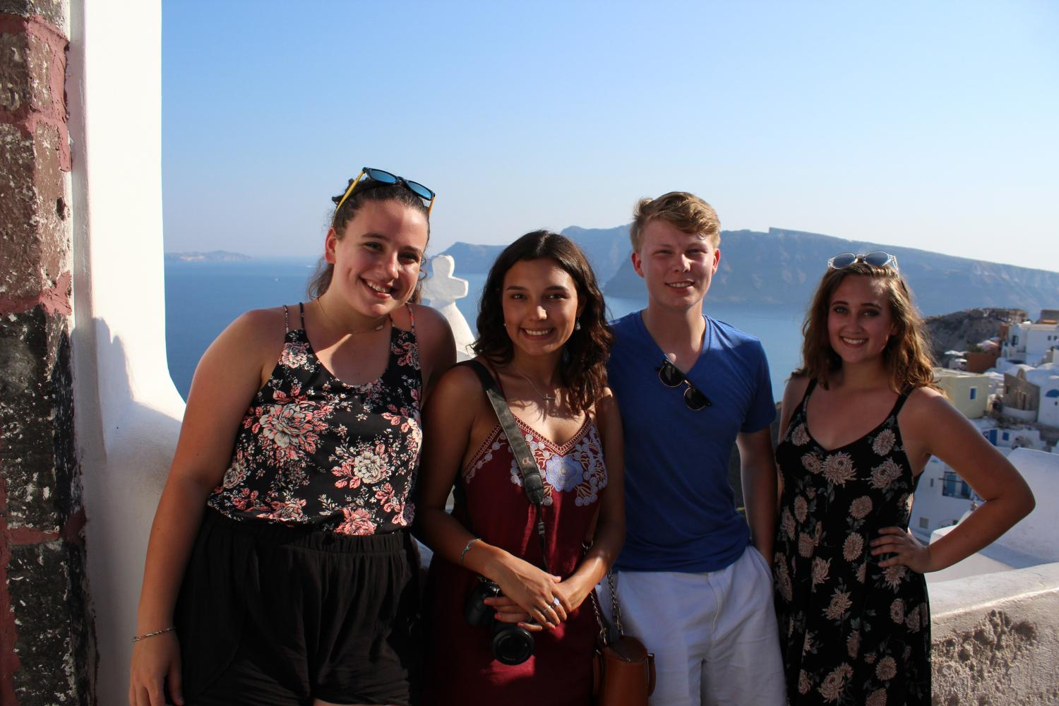 Addison Baquet, Morgan Droblyn, Coleman Allen, and Julia Austin stand with their backs to a Greek coastline. The students viewed these stunning vistas as the travelled across the Mediterranean.