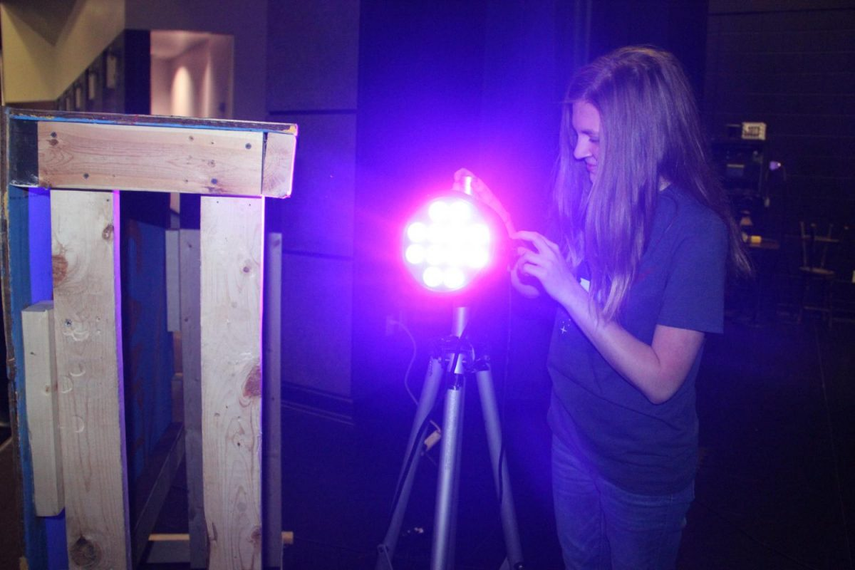 Sophomore Jamie Thornton adjusts a light on set. The theater department is currently working on Shakespeares Midsummer Nights Dream.