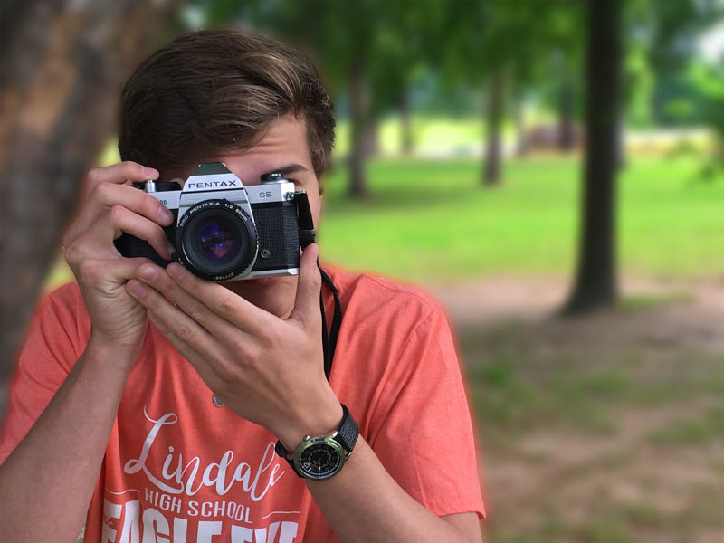 Senior Anthony Wyatt snaps a photo of another photographer. He took this photo in preparation for his trip to Costa Rica.