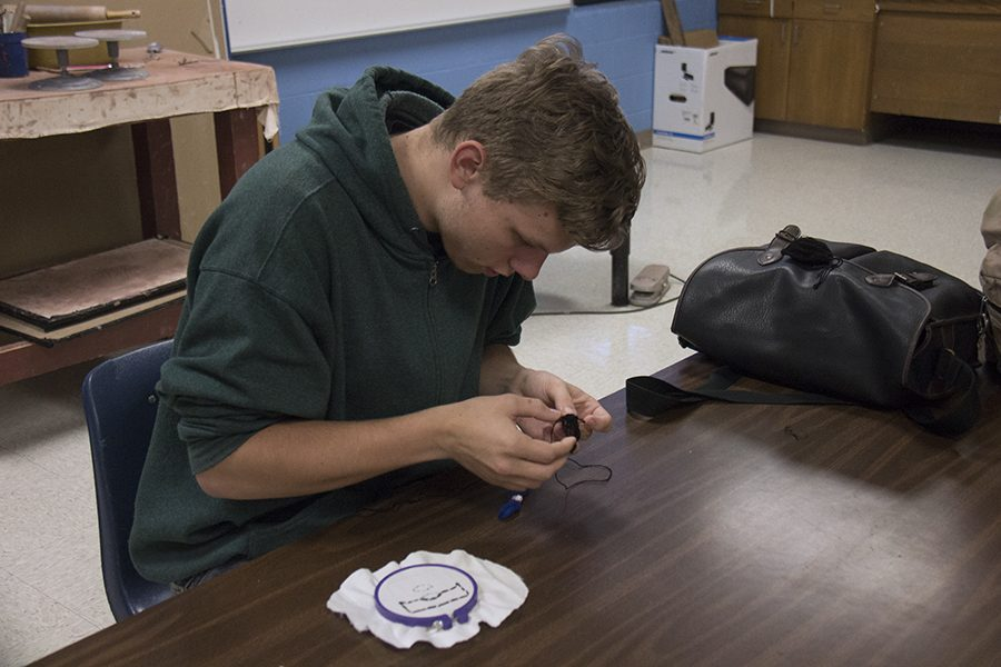 Art club member works on cross-stitching. He will be going on the art club excursion this weekend.