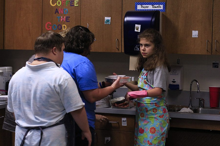 Life Skills students hand out meals to teachers during lunch. They prepared the food, took money and made change.