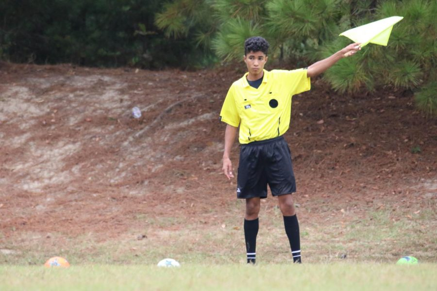 Sophomore soccer referee Salomao Saboia raises his flag to make a call. He is from Brazil, the soccer country of the world, and he has played soccer for most of his life. This is his first season refereeing.