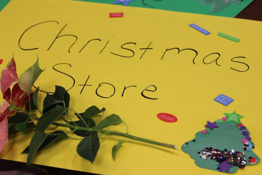 A poinsettia rests on an official store sign. The Life Skills students and sponsors opened a Holiday Store in the school library.
