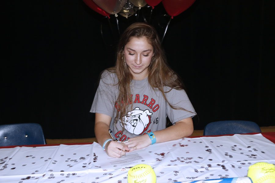Senior+Lorin+Reue+signs+for+a+softball+scholarship.+Reue+will+be+attending+Navarro+College.