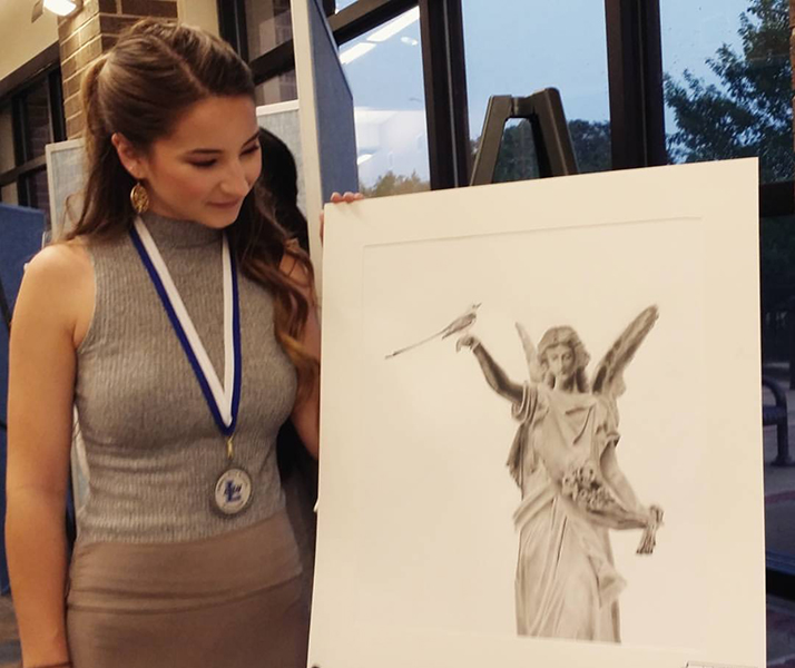 Senior Audry Nilson stands beside her portrait