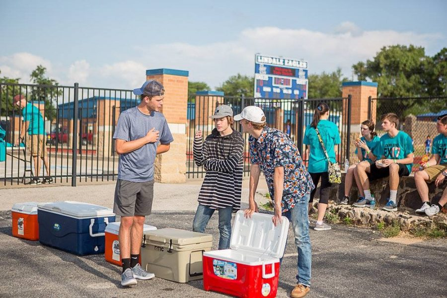 Three current seniors chat around a cooler at an LHS Project Graduation fundraiser at the end of the 2016-2017 school year. Several events and other fundraisers have been hosted to finance the senior trip and breakfast at the end of the year.