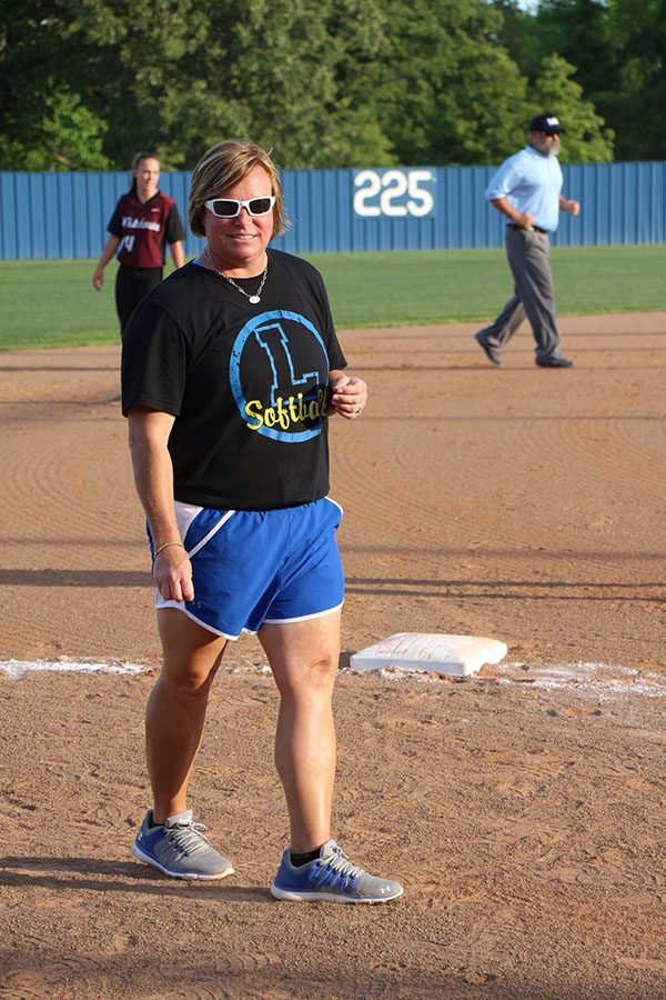 Coach Grant stands by third base to give signals to the batter at the plate. She as been the softball head coach for the past three years.