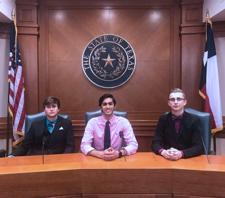 Seniors Anthony Wyatt, Ronak Desai and Evan Bewersdorf sit in a sub-committee chamber at the state Congressional Debate competition. This is the second year all three of them have competed in this event.