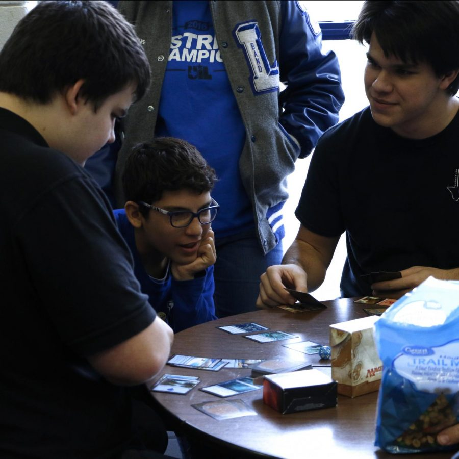 Junior Joe Adams deals a hand of the card game Magic Gathering. AFter competing at New Caney for UIL, he and a group of friends played a round of games.