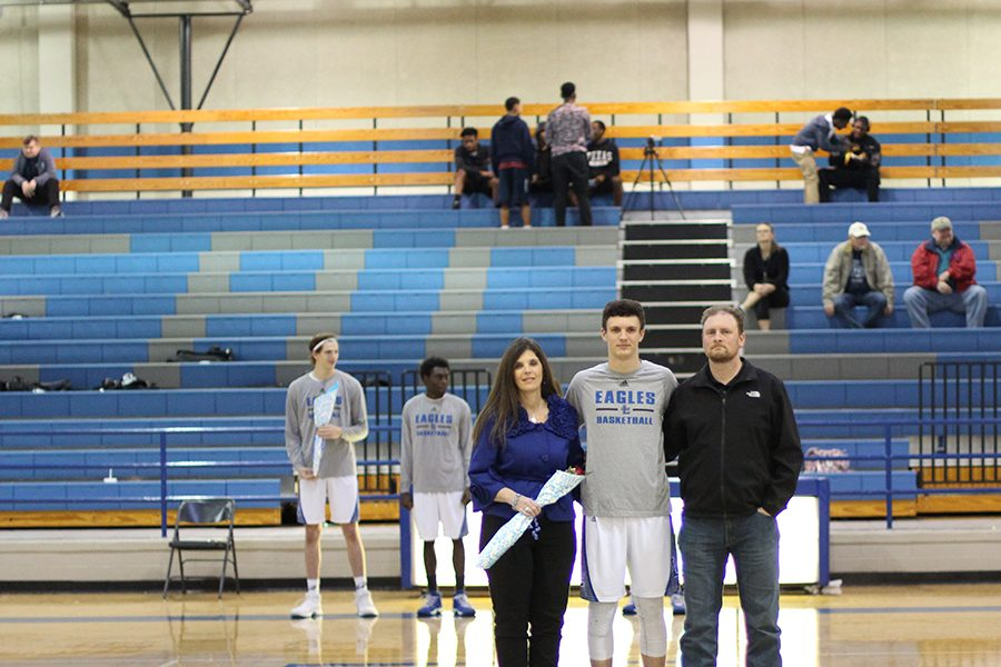 Senior Joe Noble stands with his parents on senior night. Noble plays on the varsity basketball team.