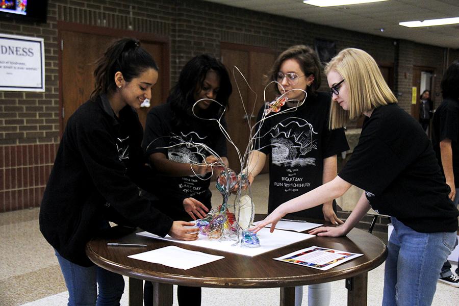 Student volunteers arrange the sculpture