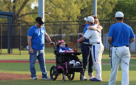 Senior Conner Heller and his mom embrace as Lucy prepares for the first pitch. Her father threw the first pitch of the game for her.