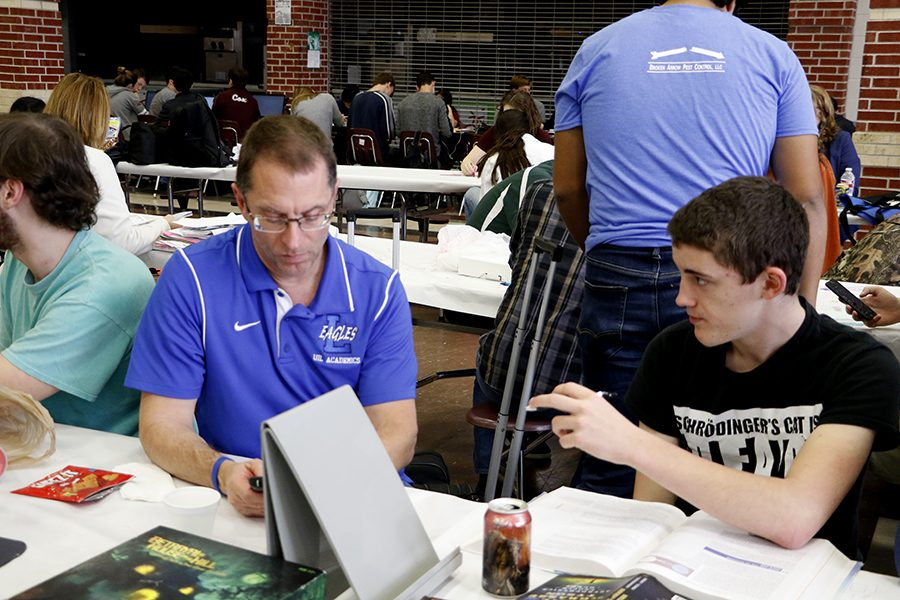Physics teacher Duane Walton assists his science UIL team. They practiced in their free time in between competitions.