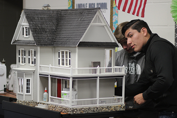 Junior Santiago Castillo puts finishing touches on his group's model house. Four houses were built with real-life design elements.
