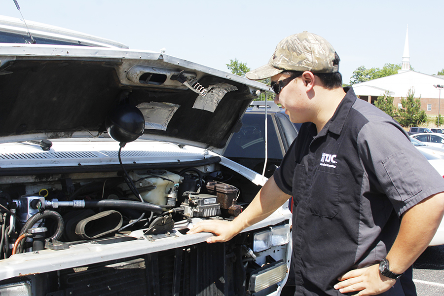 Senior Yang Curry explains his new engine. Curry installed a new engine into his van earlier this year.