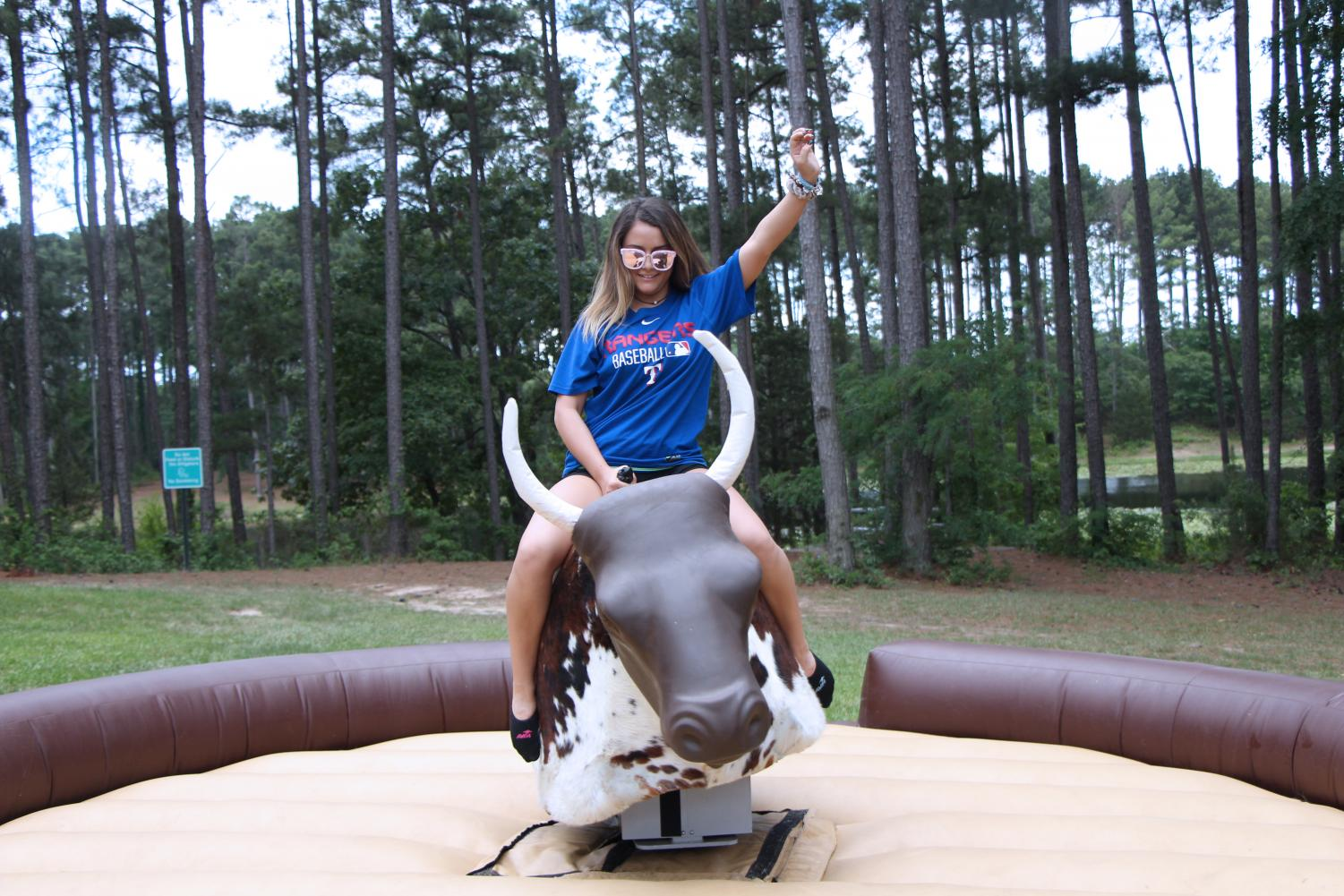 Senior Melissa Newman rides a mechanical bull during the senior picnic. Along with basketball, football, volleyball and soccer, the bull was one of the main attractions for students.