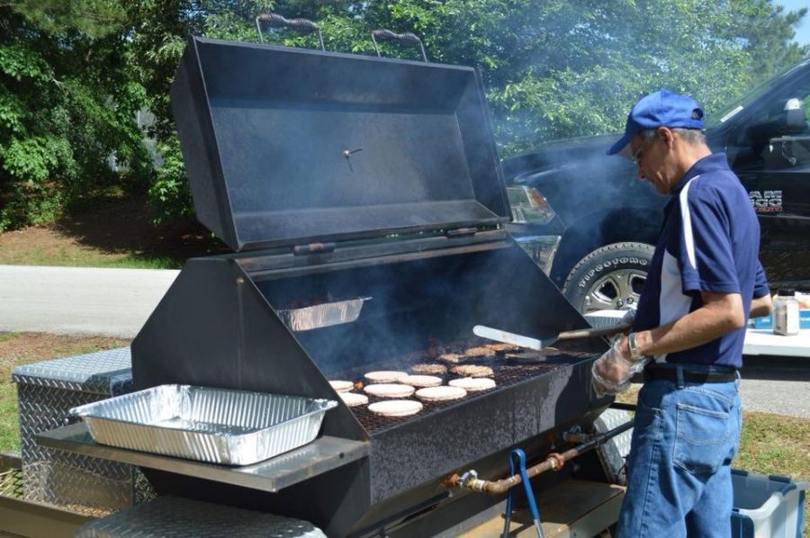 The late Jesse Rodriquez grills burgers before a tailgate party. His family will honor his legacy at the first home football game of the season.