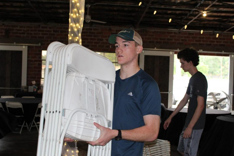 Junior+Travis+Reeves+helps+at+the+gala.+He+set+up+tables+and+chairs+for+the+event.