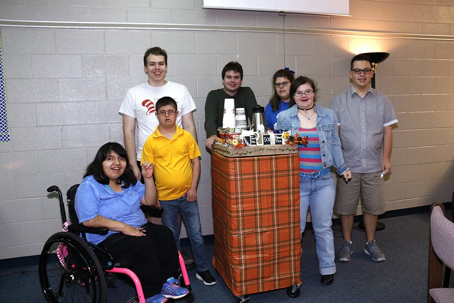 CBI students pose in front of their tea and coffee cart. They decorated it in celebration of fall.