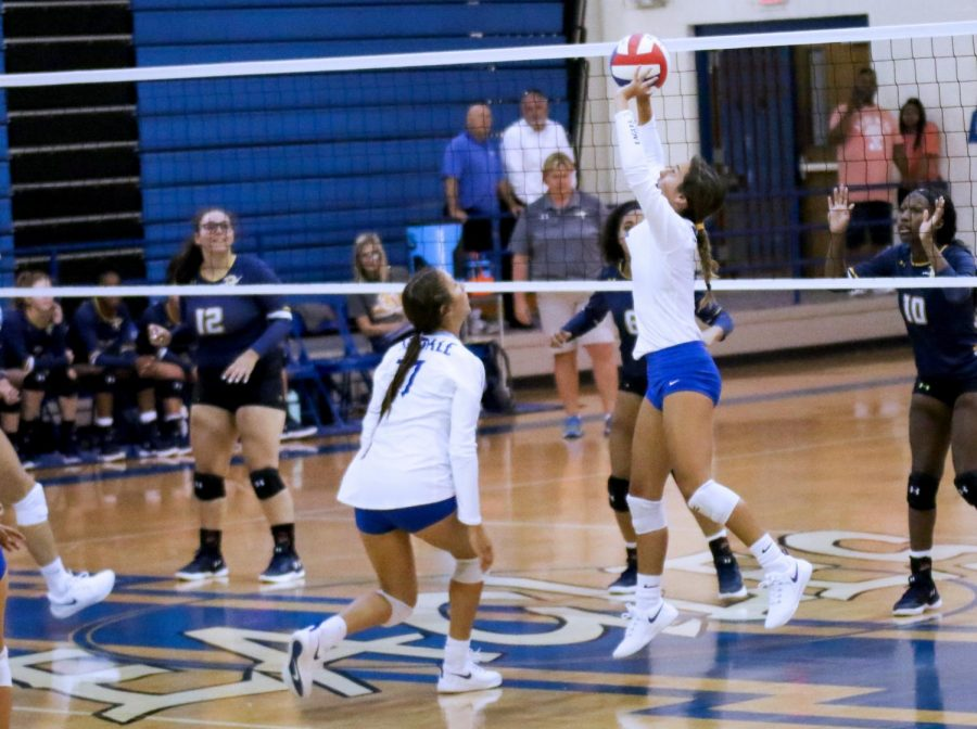 Junior Harleigh Thurman sets the ball as fellow junior London Reue prepares to spike it down. The varsity team beat Pine Tree in straight sets with scores of 25-23, 25-14, and 25-14.