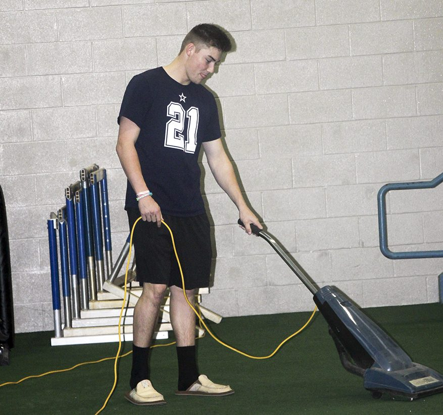 Senior Chase Rozell vacuums the gym. He participates every week in Give Back Days.