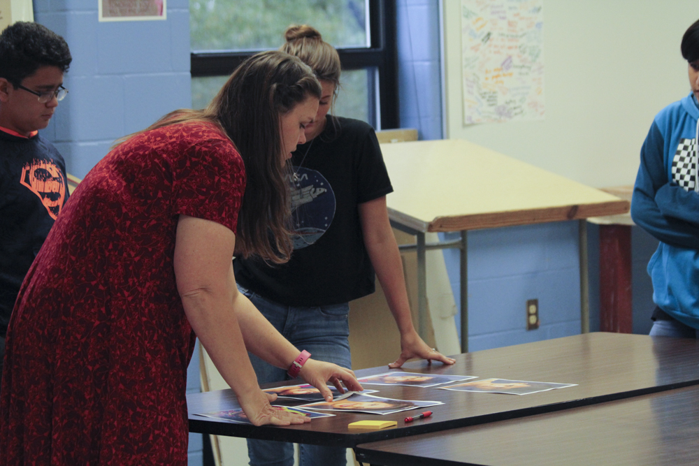 Rebecca Harrison helps art students choose which refugees to draw portraits of.  These are used as references for the artists to create their work.