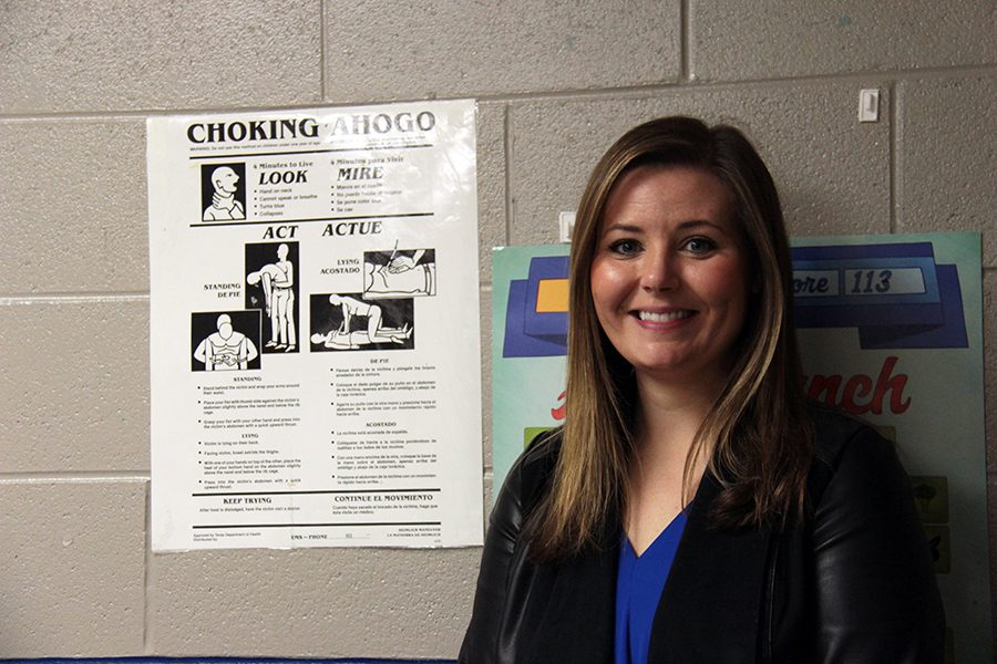 Assistant Principal Macie Thompson poses with an instructional sign. She performed the maneuver listed.