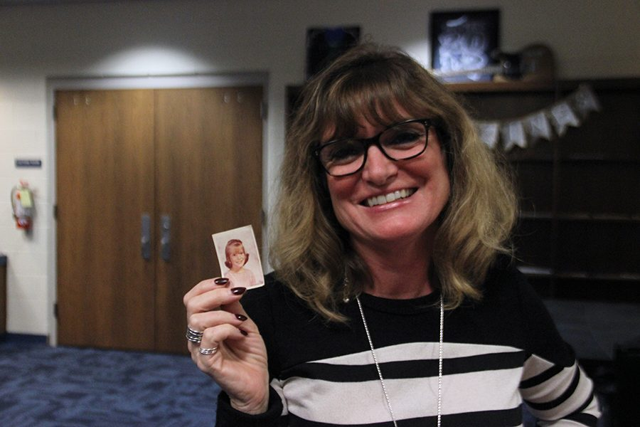 Technology specialist Beth Huse poses with an image of herself as a child. In the image, she had recently moved back to the United States.