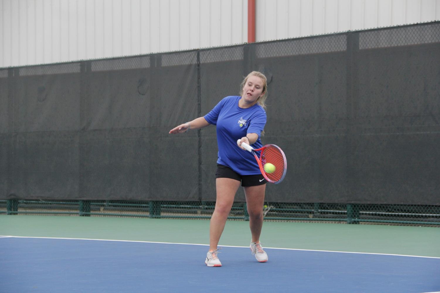 Senior Caroline Colliver volleys the ball at the bi-district game against Jacksonville. The varsity tennis team will play either Whitehouse or Kaufman at the regional tournament Monday.