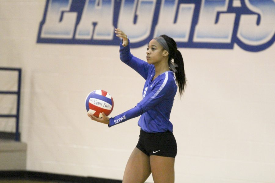 Sophomore Kalaya Pierce begins tossing the ball in the air for a serve. The varsity team played a tough, full five set match against Longview, and came out victorious in the end.
