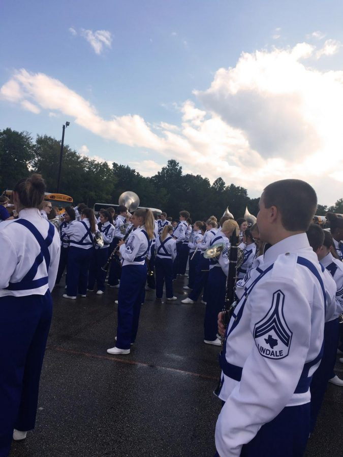 The band stands on the parking lot after putting on their uniform. They then proceeded to go to the warm-up area.