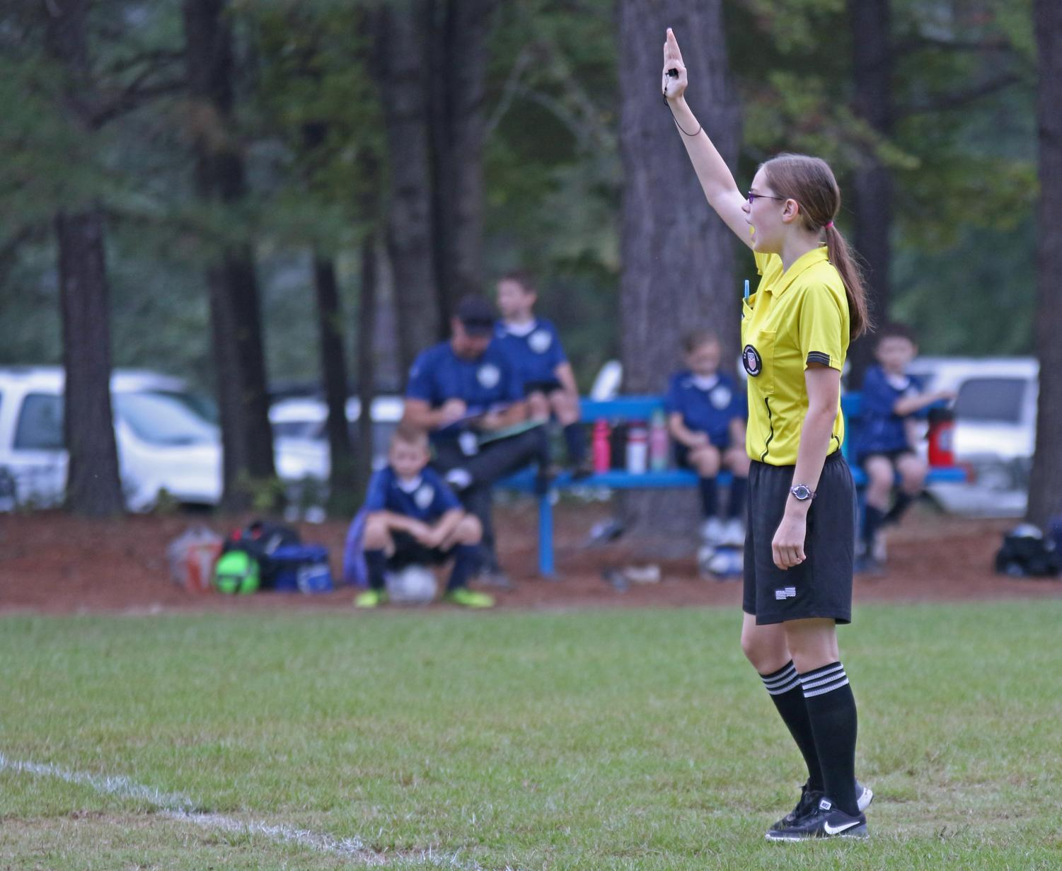 Junior soccer referee Colleen Starkey makes a foul call in a youth recreational soccer game. She has been a referee for five seasons, all with the Lindale Soccer Association.