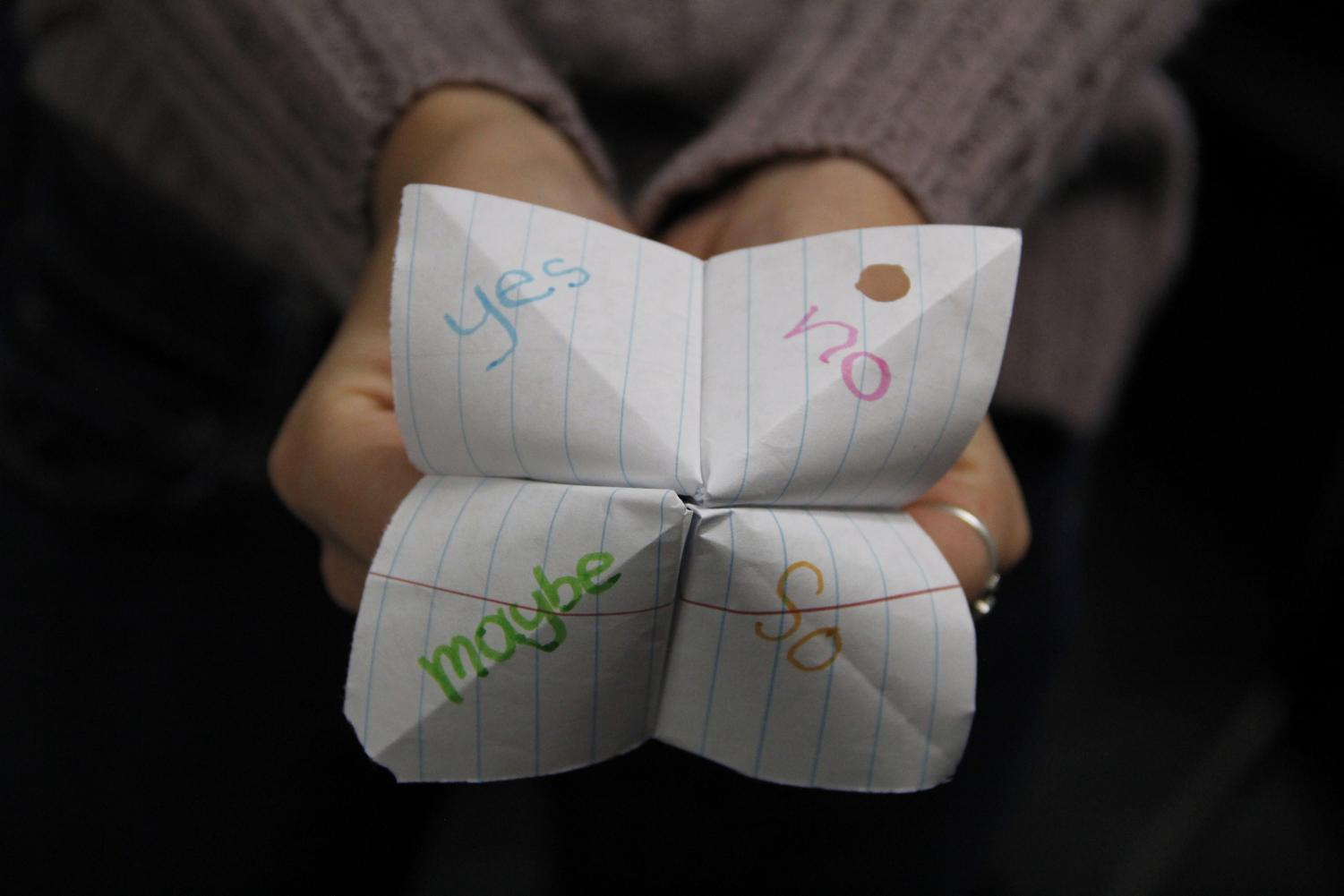 A student holds up a fortune teller with choices written. This is a representation of what I have to go through.