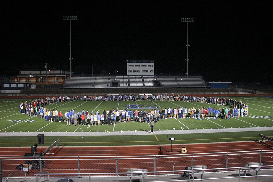 Students gather in a prayer circle in the middle of the football field. FCA promotes Fields of Faith every year.